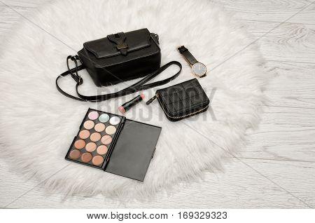 Eyeshadow wallet lipstick watch and black handbag on a white fur. Fashion concept