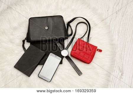 Open black bag with dropped things notebook mobile phone watch and red purse. The white fur on background top view. fashion concept