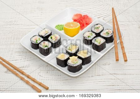 Square plate with a set of rolls on a wooden table. Chopsticks ginger lemon. Side view