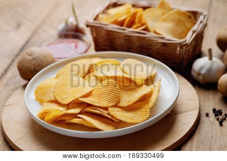 Crispy potato chips, potato and sauce on a wooden table