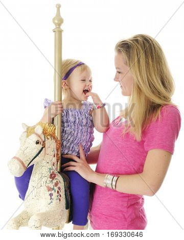 An adorable 2-year-old laughing on a carousel horse with her mom standing by her side.  On a white background.