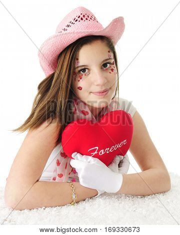 An attractive teen girl in a pink cowgirl hat, her face adorned with sparkly hearts and hugging a