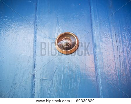 Close up door peephole on blue wooden texture