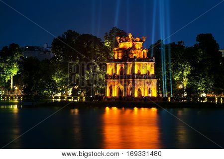 Hanoi Vietnam. Illuminated Turtle Tower at Hoan Kiem Lake in Hanoi Vietnam. Tree at the background at night