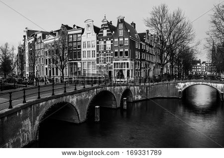 Amsterdam Netherlands canals and bridges. Night view of Keizersgracht and famous touristic place. Black and white