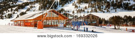 Slopes of Winter Resort El Tarter and Pyrenees Mountains in Andorra la Vella. Restaurant and cafe building unidentified people skiing