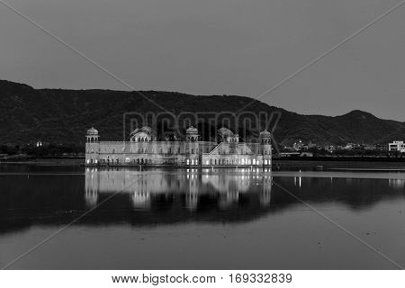 Illuminated Jal Mahal palace at night in Jaipur India. Popular landmark surrounded by water. Mountains at the background. Black and white