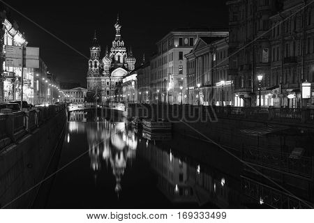 Illuminated Church on Spilled Blood with dark sky in Saint Petersburg Russia. Griboyedov canal and busy street with many cafes restaurants and shops. Black and white