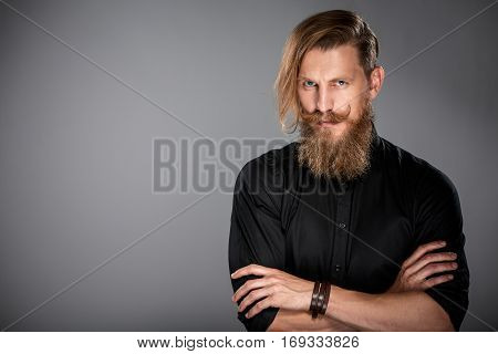 Closeup portrait of hipster man with beard and mustashes wearing black shirt gazing at camera, over grey background