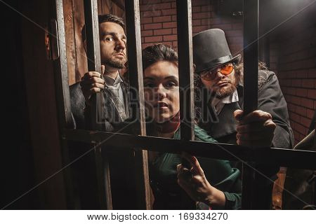 Two Gentlemen And A Lady Behind Bars In The Prison.