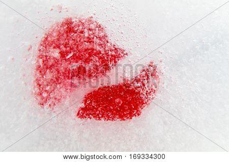 Red broken heart frozen in ice, macro, selective focus