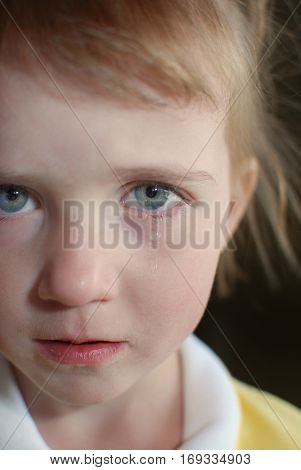 Little girl portrait crying with tears rolling down cheek