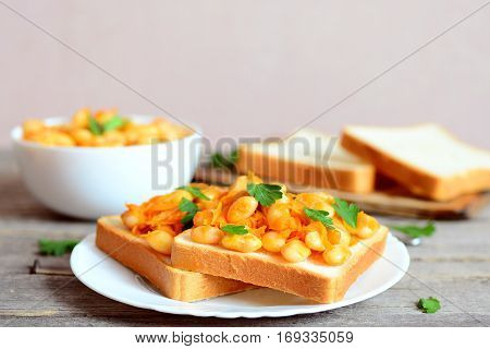 Homemade open sandwiches with baked white beans. Beans baked with carrots, garlic and tomato sauce in a bowl, bread slices, fresh parsley on a rustic wooden table. Vegetarian or vegan sandwiches