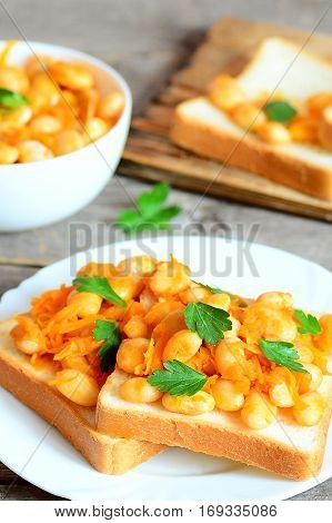 Open sandwiches with baked beans, carrots and parsley on a plate. Baked white beans in a bowl, bread slices, spoon on vintage wooden table. Vegetarian meal for better health. Vertical photo