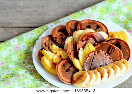 Tasty cacao pancakes with fruit. Baked cacao pancakes with syrup, sliced fresh bananas and apples on a white plate and on vintage wooden table. Pancake day breakfast idea. Closeup