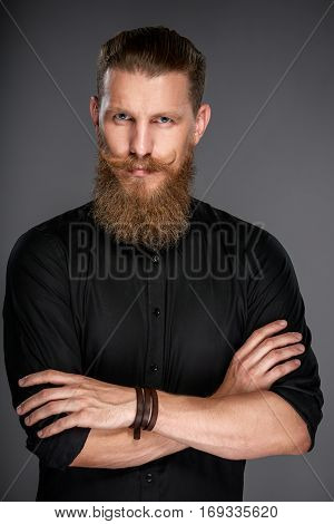 Portrait of hipster man with beard and mustashes standing wiht folded hands