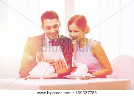 restaurant, couple, technology and holiday concept - smiling young woman looking into boyfriends or husbands menu on tablet pc computer