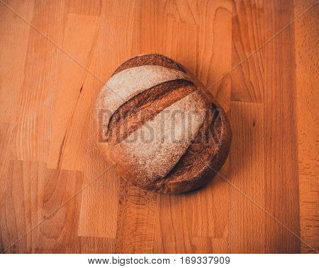 Rye bread on a wooden table. Top view. Fresh fragrant crispy bread.  Bread on cutting board closeup. Bread rye on an old background.