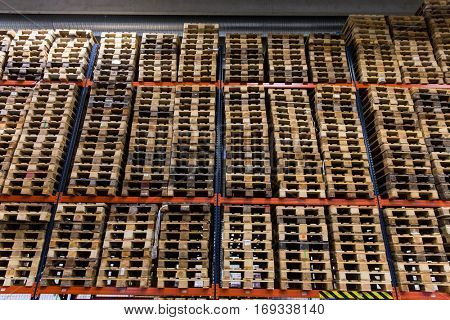 logistic, storage, shipment, industry and manufacturing concept - wooden cargo pallets storing at warehouse shelves