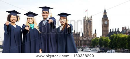 education, graduation and people concept - group of happy international students in mortar boards and bachelor gowns pointing finger at you over london city background