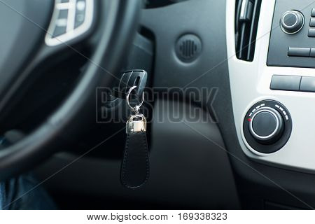 transportation and ownership concept - car key in ignition start lock