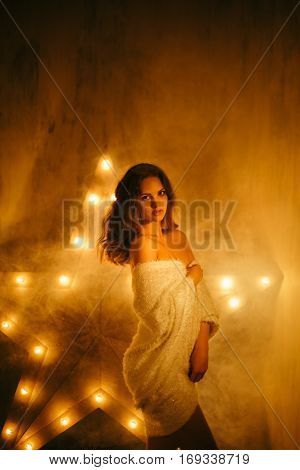 Young tender woman in white cape. Dark foggy mysterious interior with grungy wall and star on the background