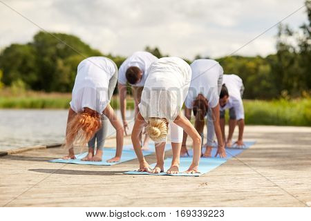fitness, sport, yoga and healthy lifestyle concept - group of people making standing forward bend on river or lake berth