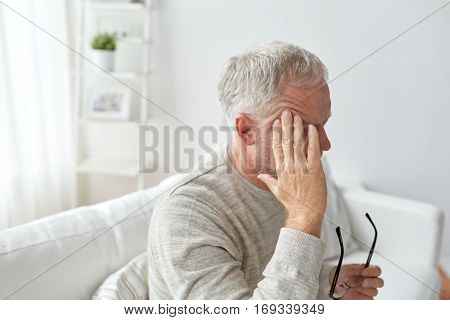 healthcare, pain, stress, age and people concept - senior man suffering from headache at home