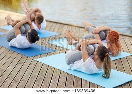 fitness, sport, yoga and healthy lifestyle concept - group of people making knee press pose on river or lake berth