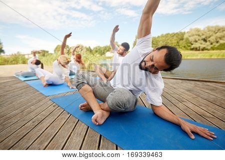 fitness, sport, yoga and healthy lifestyle concept - group of people exercising and stretching on river or lake berth
