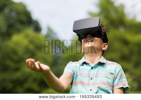 childhood, augmented reality, technology and people concept - boy with virtual headset or 3d glasses playing game outdoors at summer