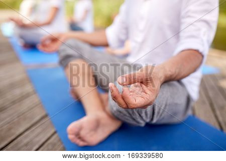 fitness, sport, yoga and healthy lifestyle concept - close up of people meditating in easy sitting pose on river or lake berth