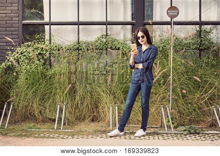 young asian woman wearing blue jeans and sunglasses standing outside using her smart phone vintage color style