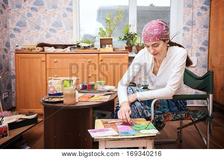Woman enthusiastically paints a picture in her studio.