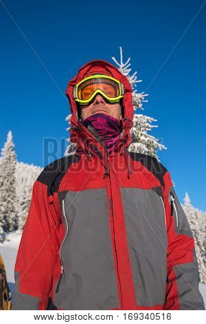 Portrait of man traveler wearing in a goggleswho stands in the winter mountains on the background of blue sky. Low point of shooting.