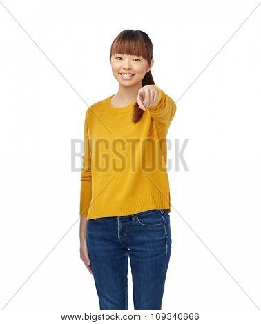 people, ethnicity, choice and gesture concept - happy asian young woman pointing finger on you over white