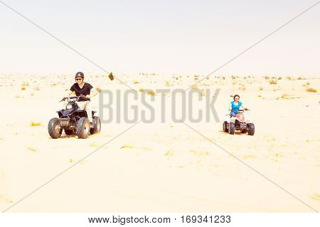 tourists riding quad bikes in the desert