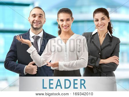 Team of business people. Word LEADER on background