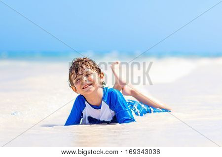 Adorable little blond kid boy having fun on tropical beach of Jamaica. Excited child playing and surfing in sun protected swimsuit in ocean on vacations.