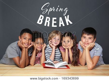 Text SPRING BREAK and children with book on dark background. Additional education concept