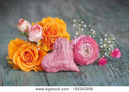 Stil life with colorful roses on an old shabby wooden table for a mothers day greeting card