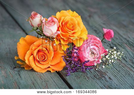 Colorful flower decoration with roses on an old rustic wooden table