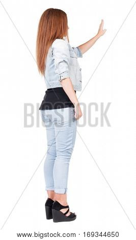 back view of woman. Young woman in jeans presses down on something. Isolated over white background. Rear view people collection. backside view of person. she holds his hand open, palm forward