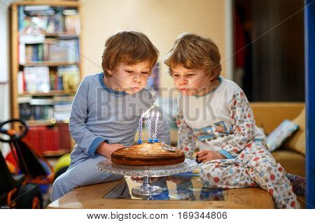 Beautiful kids, little boys celebrating birthday and blowing candles on homemade baked cake, indoor. Birthday party for siblings hildren. Happy twins about gifts