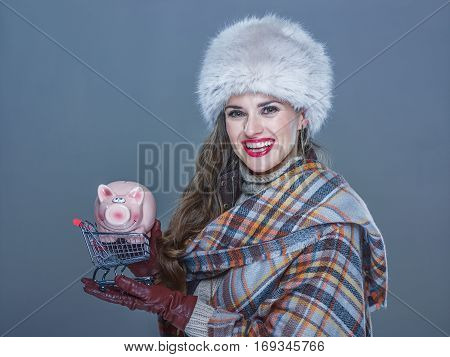 Woman Isolated On Cold Blue Holding Shopping Trolley With Piggy