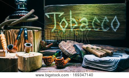 Tobacco showcase. Wooden sign above smoking pipes and cigars assortment