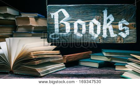 Traditional bookery shop. Assortment of old books on wood counter. Wood old-fashioned sign