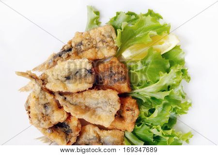 Typical dish of Neapolitan cuisine in Italy. Anchovies breaded in flour then egg fried in peanut oil. Ready meal accompanied by a green salad and lemon garnish.