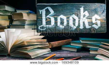 Ancient paper books in booksellers showcase. Wooden sign