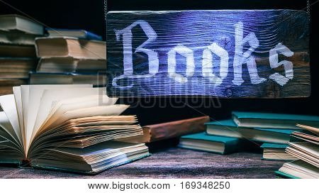 Blue-lighted wood sign of book shop. Showcase with old books